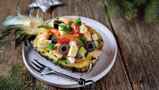 Insalata festiva di gamberi, kiwi, olive, formaggio a pasta molle, uova di quaglia, pomodorini in piatti di ananas.