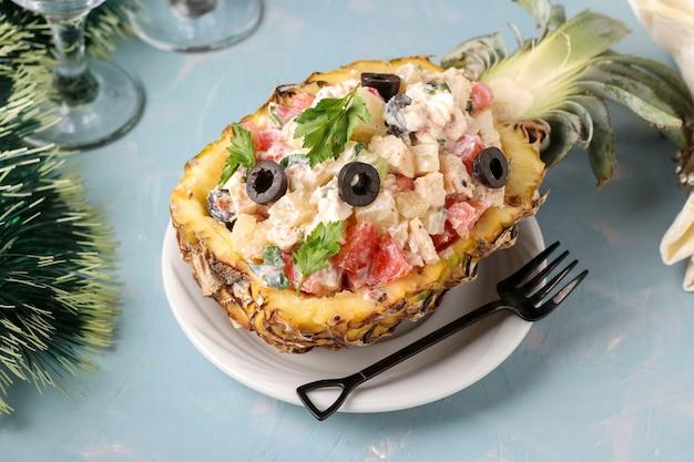 Insalata festiva con pollo a metà di ananas su sfondo azzurro, capodanno, san valentino