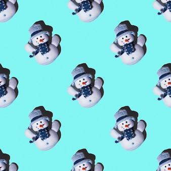 Pupazzi di neve festivi senza cuciture giocattolo su uno sfondo azzurro, disposizione quadrata, vista dall'alto. può essere usato come biglietti di natale e capodanno, sfondo per il design, carta da regalo.