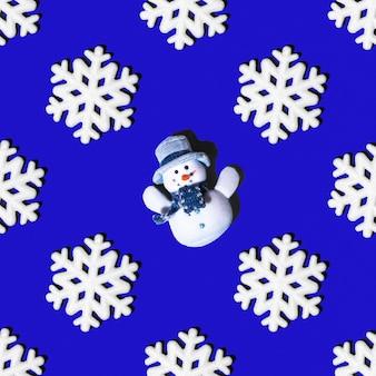 Fiocchi di neve bianchi e pupazzo di neve festivo senza cuciture su sfondo blu, disposizione quadrata, vista dall'alto. può essere usato come biglietti di natale e capodanno, sfondo per il design, carta da regalo.