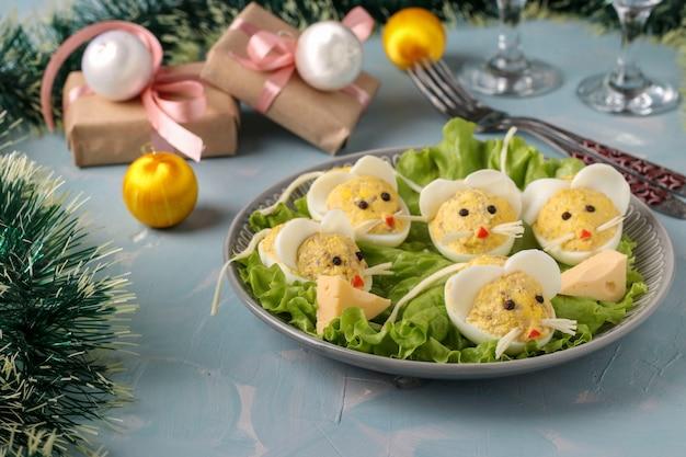 Spuntino festivo topi fatti di uova ripiene con fegato di merluzzo su sfondo azzurro, cibo simbolico per il nuovo anno, orientamento orizzontale