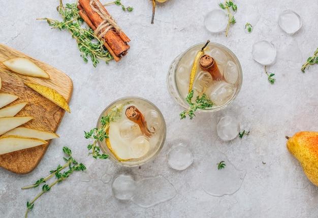 Cocktail speziato estivo festivo con pere e timo su fondo beige chiaro. vista dall'alto