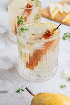 Cocktail speziato estivo festivo con pere e timo su fondo beige chiaro.