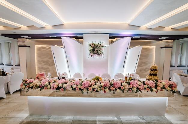 Tavolo festivo sposi decorato con composizione di fiori e verde nella sala del banchetto nuziale. festa di matrimonio in tenda.