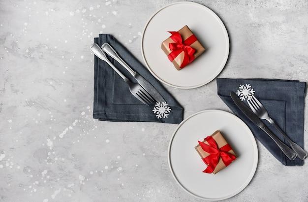 Tavola festiva, pranzo di natale. piatto artigianale bianco, decoro fiocco di neve e regalo sul tavolo di pietra