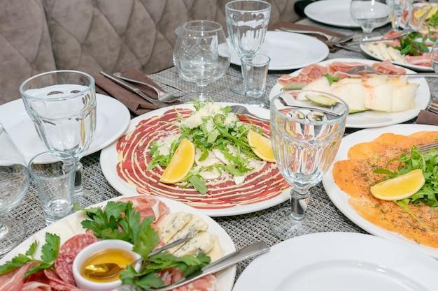 Tavola festiva, cena in famiglia con antipasti italiani serviti - salmone marinato, hamon, carpaccio, pera, basilico. tablescape.