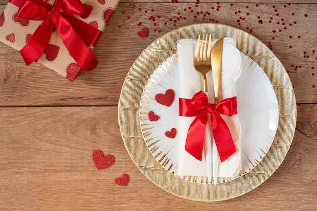 Tavola festiva per san valentino con forchetta, coltello, fiocco rosso, regalo e cuori su un tavolo di legno. spazio per il testo. vista dall'alto