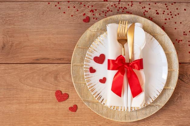 Tavola festiva per san valentino con forchetta, coltello, fiocco rosso e cuori su un tavolo di legno. spazio per il testo. vista dall'alto