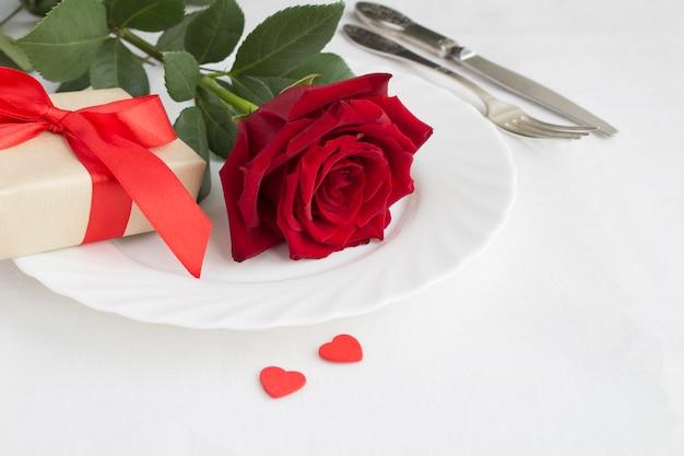Regolazione festiva della tavola per san valentino con rosa rossa e regalo