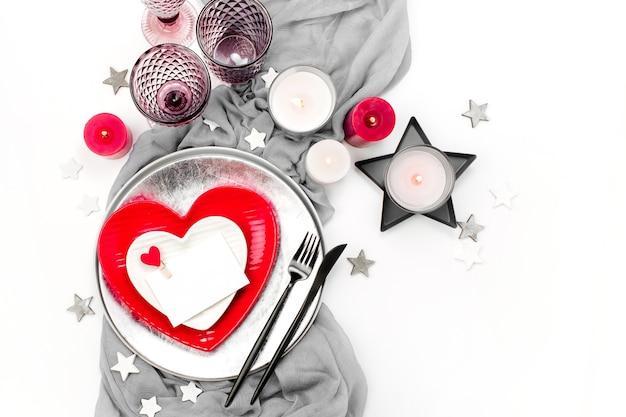 Regolazione della tavola festiva. piatti bianchi e rossi a forma di cuore, bicchieri per bevande, candele e posate sfondo bianco. san valentino o concetto di matrimonio