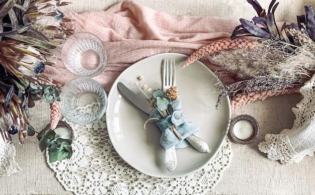 Regolazione festiva della tavola con rametti di fiori secchi ed elementi decorativi.