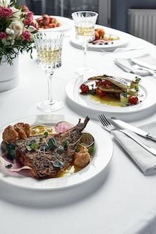 Tavolo festivo con piatti di pesce e bicchieri di vino, branzino alla griglia su un tavolo luminoso con vino bianco, concetto di tavolo da matrimonio.