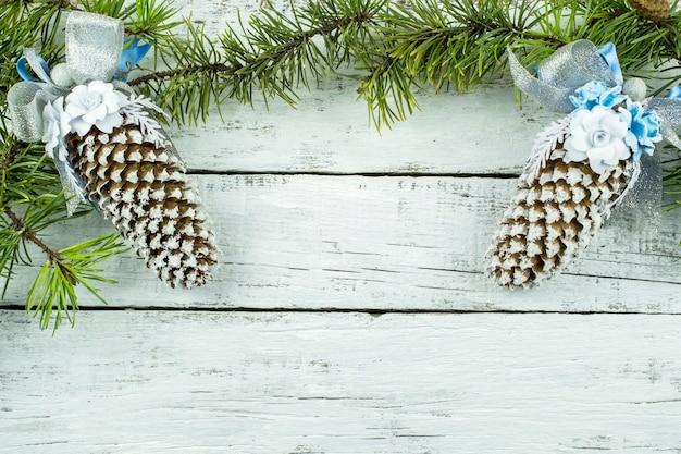 Fondo di legno bianco festivo per congratulazioni con spazio per testo, ramo di abete e coni decorativi.