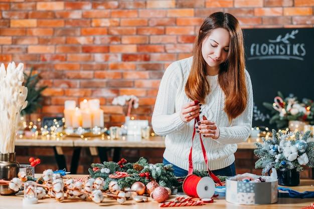 Design degli interni invernale festivo. fiorista professionista che utilizza nastro, ramoscello di abete per creare decorazioni natalizie.