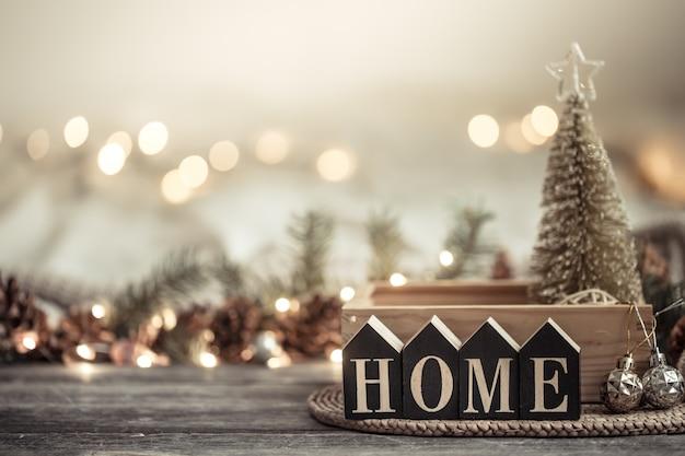 Festivo con luci e la casa di iscrizione su un tavolo di legno. con oggetti di arredamento festivo.