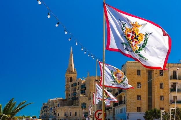 Strada addobbata a festa con le bandiere di tutti i gran maestri del sovrano militare ordine di malta nella città vecchia di la valletta, malta