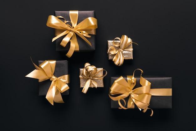 Scatole regalo dorate avvolte a festa su sfondo nero. stile piatto. concetto di vacanza e venerdì nero.