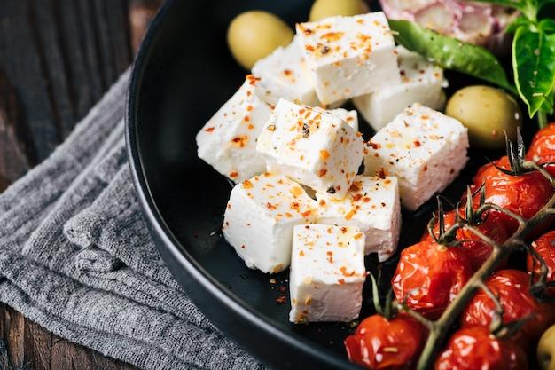Formaggio feta e pomodorini al forno, basilico e olive, insalata, fuoco selettivo, primo piano