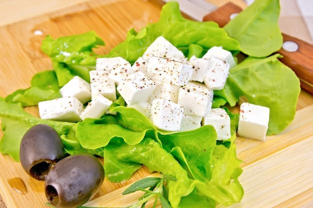 Formaggio feta, spezie, lattuga verde, olive, coltello su tavola di legno di fondo e panno