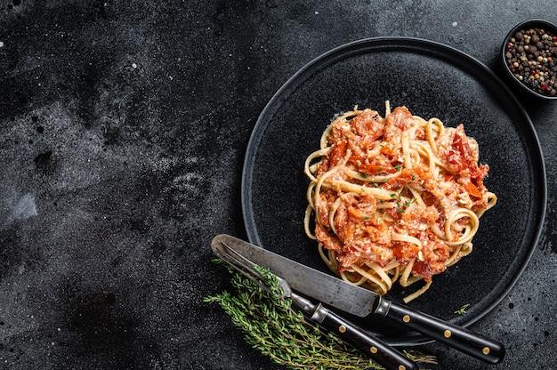 Feta con pomodorini al forno su un piatto. sfondo nero. vista dall'alto. copia spazio.