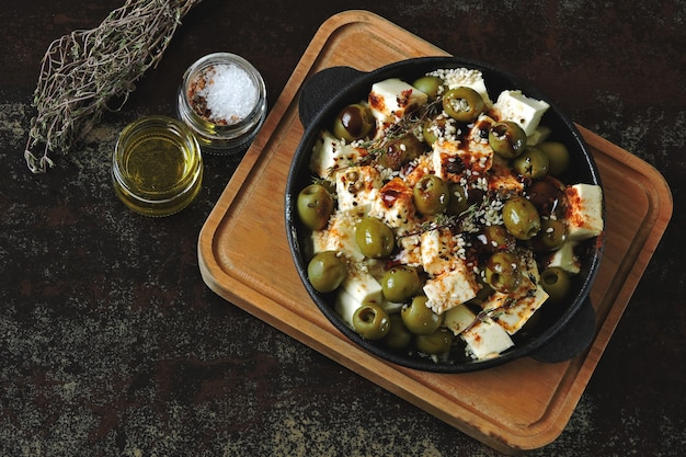 Pezzi di feta cotti con olive e spezie. pranzo o merenda sani. dieta keto ricetta keto.