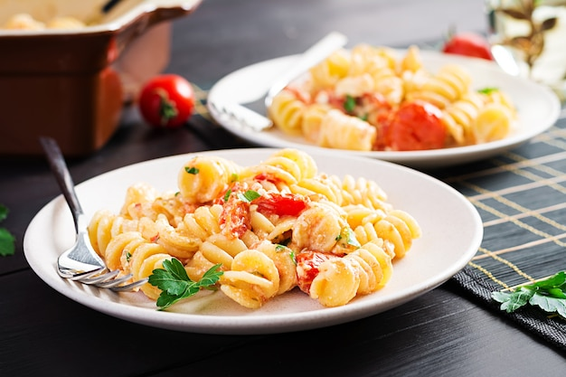 Fetapasta. ricetta di pasta al forno feta di tendenza a base di pomodorini, formaggio feta, aglio ed erbe aromatiche. impostazione della tabella.