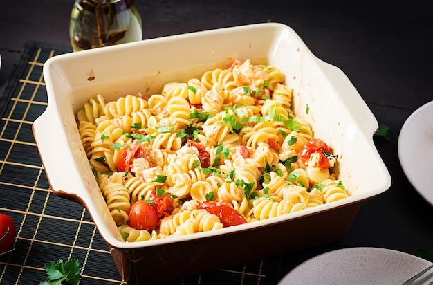 Fetapasta. trending ricetta di pasta al forno con feta a base di pomodorini, formaggio feta, aglio ed erbe aromatiche.