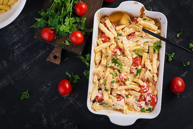 Fetapasta. ricetta di pasta al forno feta virale di tendenza a base di pomodorini, formaggio feta, aglio ed erbe in una casseruola. vista dall'alto, sopra, copia dello spazio.