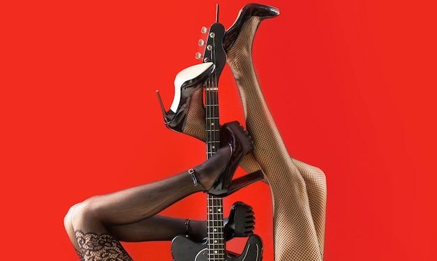 Feticismo, donna sexy, chitarra elettrica e gambe, biancheria intima. biancheria fetish. concetto di musica. gambe sexy. chitarra, chitarra elettrica. festival di musica, musica dal vivo, concerto. strumento sul palco e banda.