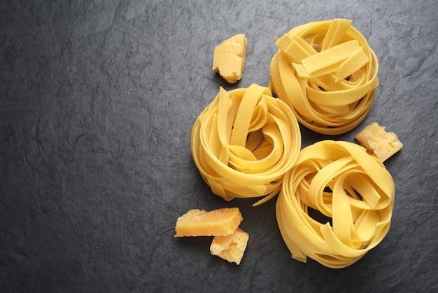 Fettuccine al parmigiano su sfondo nero ardesia con copia spazio