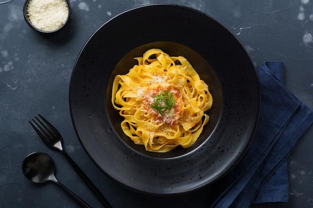 Fettuccine con salsa passat italiana tradizionale e parmigiano in banda nera su superficie scura