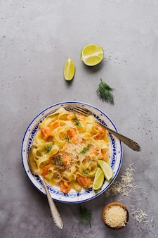 Fettuccine con salmone e parmigiano in salsa cremosa nel piatto di ceramica sulla vecchia superficie di cemento grigio