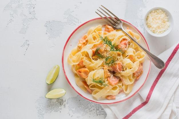 Fettuccine con salmone e parmigiano in salsa cremosa in piatto di ceramica sulla vecchia superficie di cemento leggero
