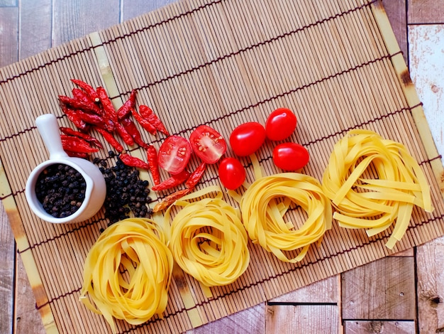 Fettuccine al pomodoro pepe nero peperoncino secco su stuoia di bambù