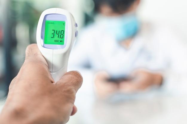Il misuratore di febbre misura la febbre per le persone con covid 19
