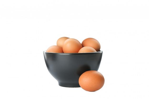 Poche uova crude del pollo in ciotola su bianco