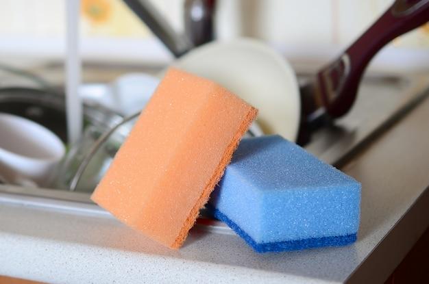 Alcune spugne si trovano sullo sfondo del lavandino con piatti sporchi