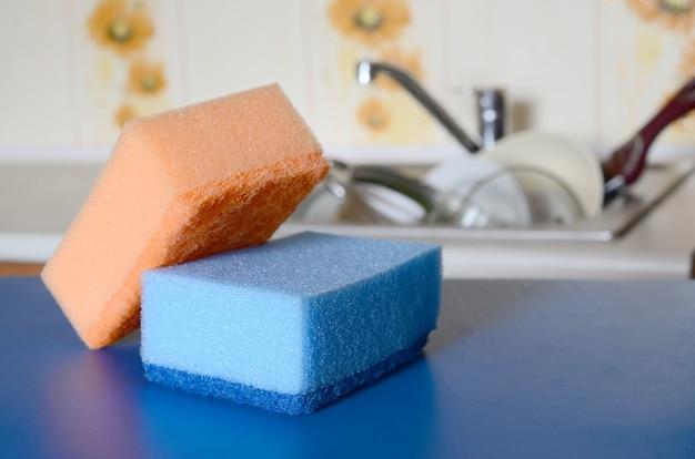 Alcune spugne giacciono sul lavandino con piatti sporchi