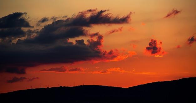 Il tramonto infuocato tra le nuvole va dietro le montagne. luminoso paesaggio estivo nella località di gelendzhik