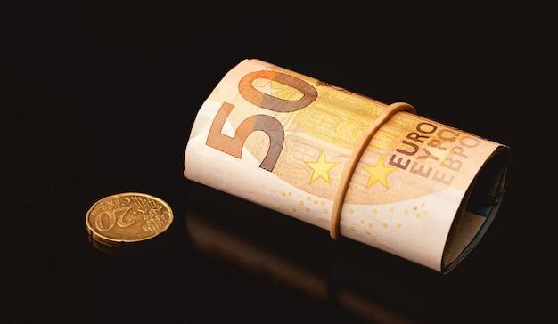 Una banconota da cinquanta euro e una moneta da un centesimo di euro su un tavolo scuro