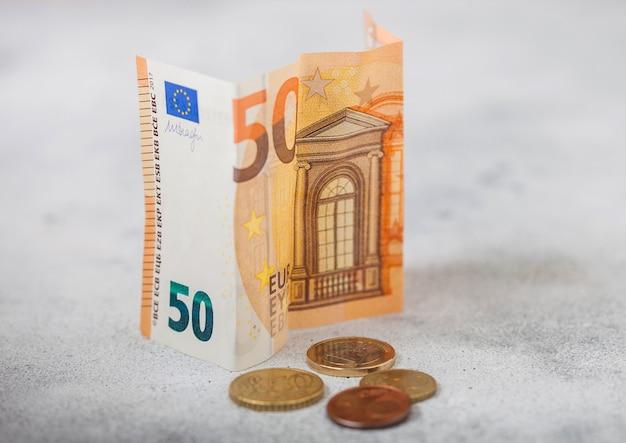 Banconota da cinquanta euro con monete