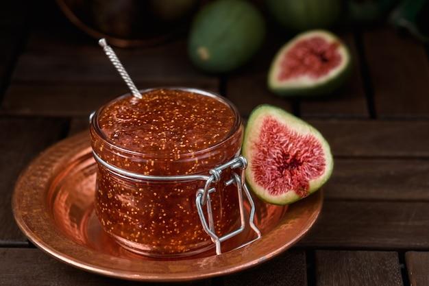 Marmellata di fichi in barattolo di vetro su piatto turco in rame, mezzo fico fresco accanto e frutta in sottofondo