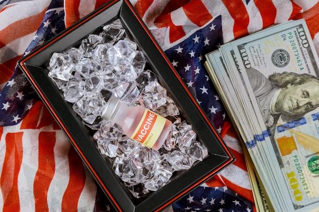 Per combattere la pandemia coronavirus covid-19 sars-cov-2 flacone di vetro per vaccinazione con bottiglia di vaccino americano su banconote da un dollaro americano
