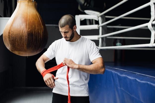 Combattente che pratica alcuni calci con sacco da boxe kick sacco da boxe sul sacco da boxe nero sfondo scuro pesa in palestra k filmati di alta qualità