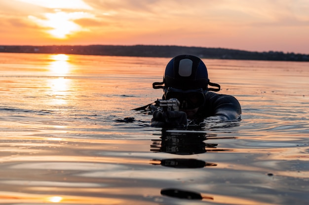 Il combattente di un'unità speciale lascia l'acqua e si prepara per l'inizio dell'operazione. tecnica mista. il concetto di instabilità nel mondo, ostilità, crisi. russia vs usa