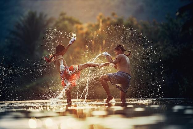 Combattente che lega il nastro intorno alla sua mano che si prepara a combattere. pugilato tailandese al fiume.