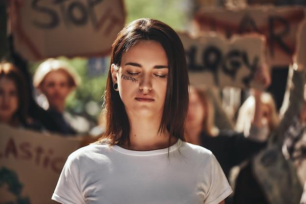 Combattendo per il pianeta pulito giovane attivista con la parola libertà scritta sul viso che tiene gli occhi