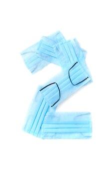 Figura 2, due maschere facciali blu protettive antibatteriche fatte a mano su un muro bianco, copia dello spazio. carattere tipografico creativo per creare nuove informazioni numeriche.