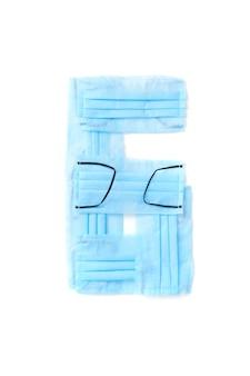 Figura 6, sei maschere facciali blu protettive antibatteriche mediche fatte a mano su un muro bianco, copia dello spazio. carattere tipografico creativo per creare nuove informazioni numeriche.