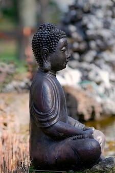La figura del buddha che siede nella posa del loto è realizzata in metallo
